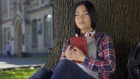 Asiatiskt flickaläsebokkapitel och entusiastiskt att le och att tycka om täppan, hobby stock video