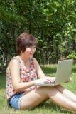 Asiatiskt flickasammanträde i trädgården som spelar en anteckningsbok Royaltyfria Foton