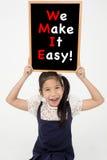 Asiatiskt flickasammanträde och hållande svart tavla royaltyfri bild