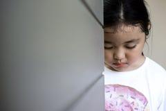 Asiatiskt flickasammanträde på golv hemma Conc pennalism och isolering arkivfoto