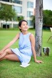 Asiatiskt flickasammanträde på gräs Royaltyfri Foto