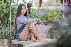 Asiatiskt flickasammanträde på soffan som kopplar av Royaltyfri Foto
