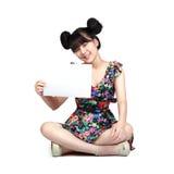 Asiatiskt flickasammanträde för tonåring på golvet som rymmer tomt papper Royaltyfria Foton