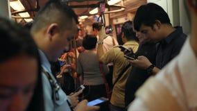 Asiatiskt folk som använder Smart telefoner och grejer inom vagnen för BTS-gångtunneldrev 4K Bangkok Thailand - 12 NOVEMBER 2017 arkivfilmer