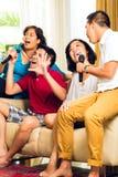 Asiatiskt folk som sjunger på karaokedeltagaren Arkivfoto