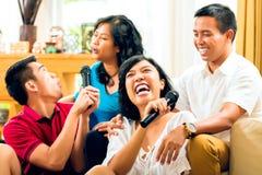 Asiatiskt folk som sjunger på karaokedeltagaren Fotografering för Bildbyråer