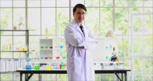 Asiatiskt forskareanseende och flytta hans kropp i laboratorium och samtal till kameran stock video
