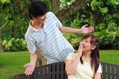 asiatiskt ge sig för par förvånar barn Arkivfoto
