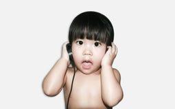 Asiatiskt gulligt behandla som ett barn kläderheadphonen för att lyssna musik Royaltyfria Foton