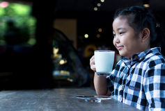 Asiatiskt gulligt dricka för flicka mjölkar i coffee shop Arkivbild