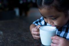 Asiatiskt gulligt dricka för flicka mjölkar i coffee shop Royaltyfri Bild