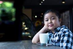 Asiatiskt gulligt dricka för flicka mjölkar i coffee shop Arkivfoto