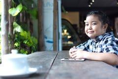 Asiatiskt gulligt dricka för flicka mjölkar och använder smartphonen i coffee shop Arkivfoto