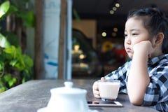 Asiatiskt gulligt dricka för flicka mjölkar och använder smartphonen i coffee shop Royaltyfri Foto