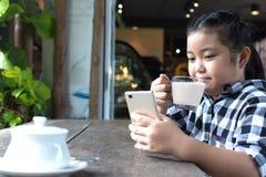 Asiatiskt gulligt dricka för flicka mjölkar och använder smartphonen i coffee shop Arkivbilder