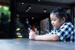 Asiatiskt gulligt dricka för flicka mjölkar och använder smartphonen i coffee shop Royaltyfri Fotografi