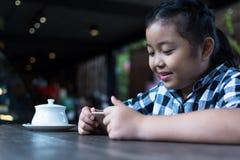 Asiatiskt gulligt dricka för flicka mjölkar och använder smartphonen i coffee shop Royaltyfria Foton
