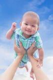Asiatiskt gulligt nyfött behandla som ett barn leende lyckligt med innehavhandmodern Royaltyfria Bilder