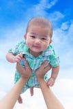 Asiatiskt gulligt nyfött behandla som ett barn leende lyckligt med innehavhandmodern på bakgrund för blå himmel Royaltyfri Foto