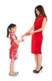 Asiatiskt kinesiskt barn som mottar den monetära gåvan från förälder Arkivbild