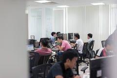 Asiatiskt kontor Team Sitting At Desk för programvarubärare arkivbild