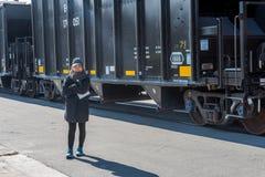Asiatiskt kvinnaanseende bredvid kolbilar fotografering för bildbyråer