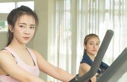 Asiatiskt kvinnaanseende på konditiontrampkvarnen med vännen Arkivfoto