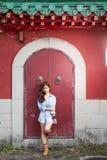 Asiatiskt kvinnaanseende vid den röda kinesiska dörren royaltyfria foton
