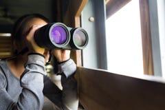 Asiatiskt kvinnabruk av kikare för birdwatching Fotografering för Bildbyråer