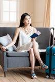 Asiatiskt kvinnahandelsresandesammanträde på soffan med resväskan och passet royaltyfria bilder