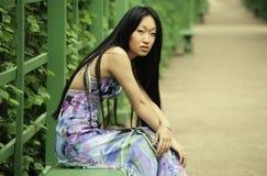 Asiatiskt kvinnasammanträde på parkerabänken Royaltyfria Foton