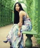 Asiatiskt kvinnasammanträde på parkerabänken Royaltyfri Bild