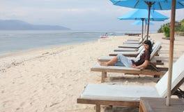Asiatiskt kvinnasammanträde på solstol på den tropiska stranden royaltyfri foto