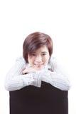 Asiatiskt kvinnasammanträde på stol och leende Arkivfoto