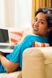 Asiatiskt kvinnasammanträde på soffan Arkivfoto