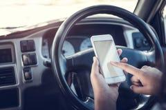 Asiatiskt kvinnasamtal av mobilen som kallar att smsa och ser på en mobiltelefon, medan sitta i hennes bil som kör under påverkan royaltyfri foto