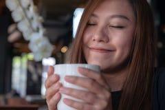 Asiatiskt kvinnaslut henne ögon till att lukta och att dricka varmt kaffe med mening bra i kafé royaltyfri fotografi