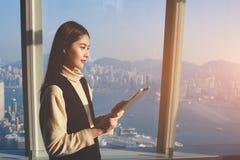 Asiatiskt kvinnligt anseende i modern kontorsinre mot fönster med cityscapesikt av New York royaltyfri fotografi