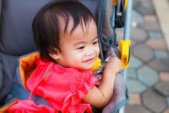 Asiatiskt kvinnligt behandla som ett barn leende i perambulator Royaltyfri Foto