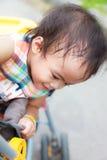 Asiatiskt kvinnligt behandla som ett barn leende i perambulator Arkivbilder