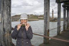 Asiatiskt kvinnligt fånga krabbor på Whitby West Pier North Yorkshire, Engla royaltyfri foto