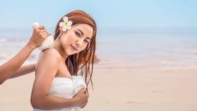Asiatiskt kvinnligt ha massage och varm kompressbehandling på stranden vid sjösidan royaltyfria bilder