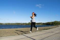 Asiatiskt kvinnligt jogga runt om sjön Arkivfoto