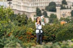 Asiatiskt kvinnligt turist- anseende i gröna buskar på en synvinkel upp höjdpunkten som tar en panorama- selfie Fotografering för Bildbyråer