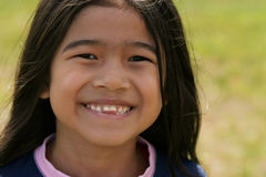 asiatiskt le för flickaleende som är toothy Arkivbild