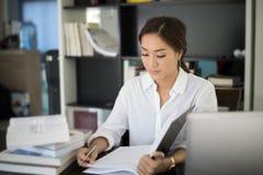 Asiatiskt le för kvinnastudent och övre handtecken och läsning a för duns Arkivfoto