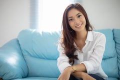 Asiatiskt le för kvinnor som är lyckligt för avkoppling på soffan hemma arkivbild