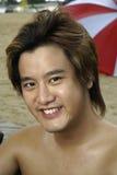 asiatiskt le för strandman fotografering för bildbyråer