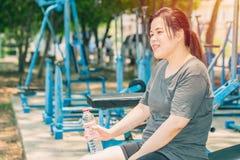 Asiatiskt leendekvinnadricksvatten efter genomkörare arkivbilder
