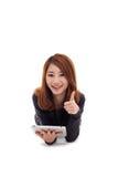 Asiatiskt ligga för kvinna besegrar med tabletPC och visningtumen. Royaltyfria Bilder